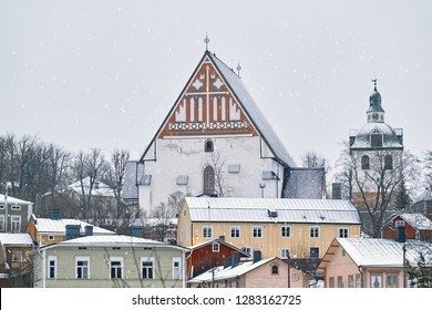 Old historic Porvoo, Finland with wooden houses and medieval stone and brick Porvoo Cathedral under white snow in winter.