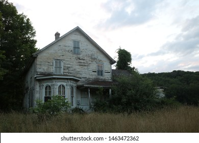 Old historic rustic abandoned wooden farm house in New England farm fields