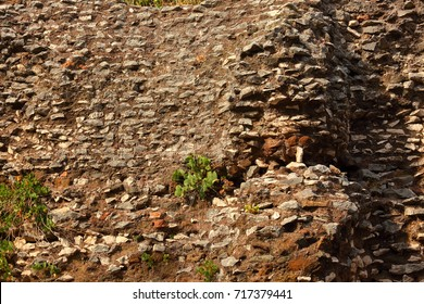 Old historical broken brick wall background in sunny summer day