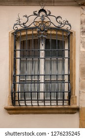 Old historical building with a lattice made of steel in front of the window