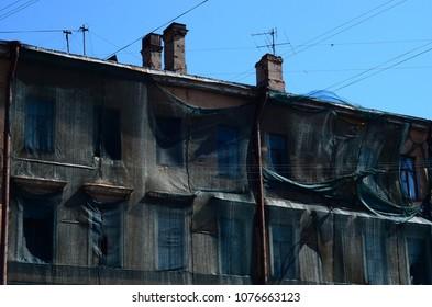 Old historical building under rekonstraction, covered black  safety mesh. Sankt-Petersburg, Russia