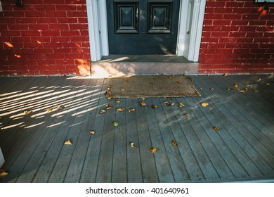 Old historical house entrance with autumn leaves on wooden deck.