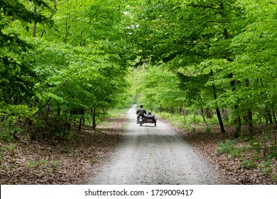 Old historical military motorcycle with sidecar classic on a beautiful dirt path in a green trees forrest in Poland (Europe) on a nice and sunny spring summer day