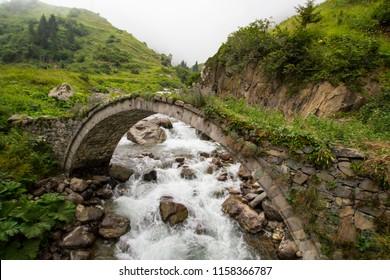 Old historical stone bridge on river under the fog at black sea region of Turkey. Historical Ottoman bridge Taskopru in Senyuva, Cinciva in Armenian, over the Firtina river near Camlihemsin in Rize pr