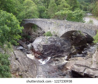 Old historical stone bridge on river in forest ravine of Scotland.