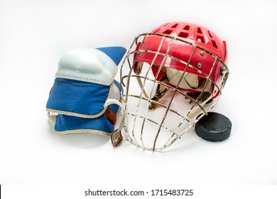 Old hockey helmet gloves and puck on a white background isolated.