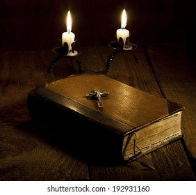 Old Holy Bible, candles and Crucifix on wooden background.
