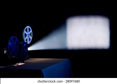 Old home film projector, running and projecting blank movie on a screen with visible  beam of light