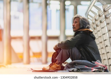 Old homeless man sitting on floor in public path way. He looking Depressed and Hopeless