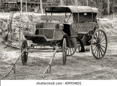 An old horse drawn buggy sitting in a barnyard. Black and white photo.