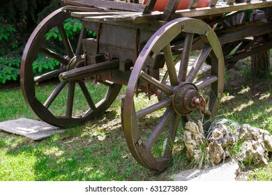 the old horse-drawn carriage converted into a flowerbed of spring flowers standing on the green grass