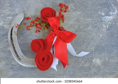 An old horseshoe decorated with red roses made of felt with red and white ribbons on a worn and scratched steel background. Copy space. Good for the Kentucky Derby in May.