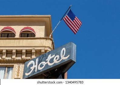 Old Hotel sign and American Flag with background of clear blue sky