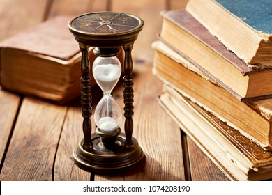 old hourglass with books on wooden table