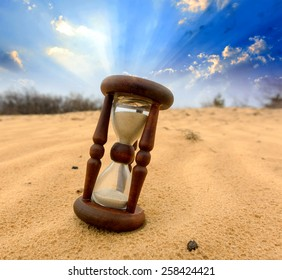 Old Hourglass in desert on sand
