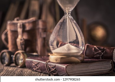 Old hourglass and journal with compass and binocular
