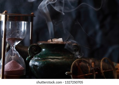Old hourglass and spectacles near extinguished candle with smoke