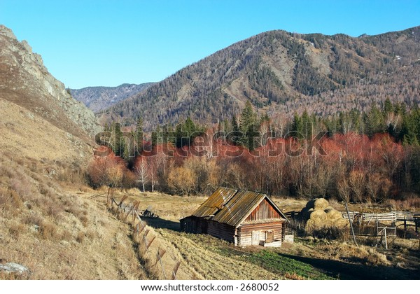 Old house, blue sky and mountains. Altay. Russia.
