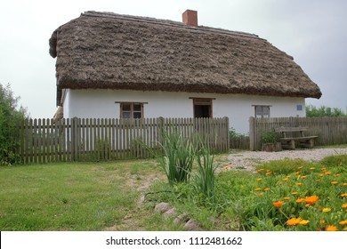 Old house (cottage, hut) with small garden with flowers and other green plants, building made of wood, white, with thatched roof, in front of it fence