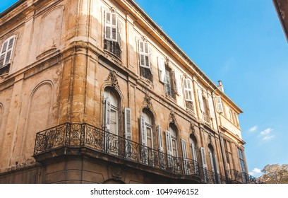 Old house in decay with forged balcony railings in Aix-en-Provence, France