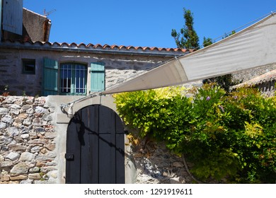 Old house facade with stones wall, foliage and flowers, blue shutters, dark door wooden, sail sunshade, in Noirmoutier island village. Vendee, France