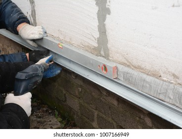 Old house foundation wall repair and renovation  with installing metal sheets for waterproofing and protect from rain. Contractors with Foundation repair.