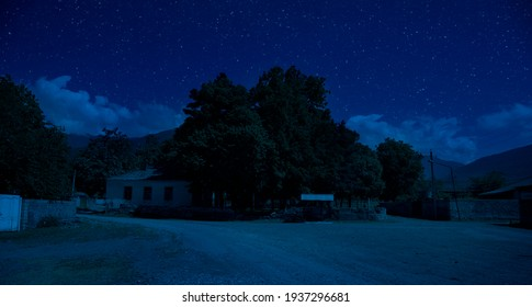 Old house with a Ghost in the forest at misty night or Night scene with House under moon. Old mystic building in dead tree forest.