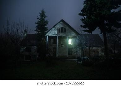 Altes Haus mit Geist in den Wald nachts oder Abandoned Haunted Horror House in Neg. Altes mystisches Gebäude in totem Baumwald. Nachts Bäume mit Mond. Surreale Lichter. Horror-Halloween-Konzept