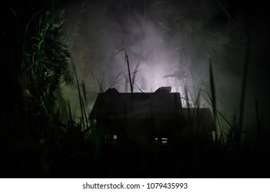 Old house with a Ghost in the moonlit night or Abandoned Haunted Horror House in fog. Old mystic villa with surreal big full moon. Horror Halloween concept. Selective focus