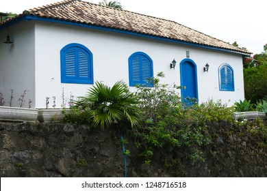 Old house in Ilhabela white with tiles and doors and windows painted blue, Ilhabela, Brazil.