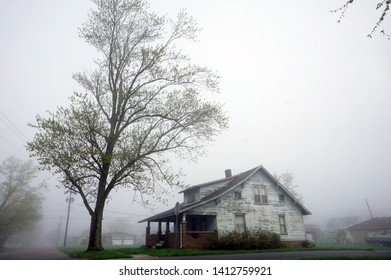 Old House on the Corner in the Fog with Large Tree in Front