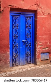 Old house with a red wall and a blue ornated door in the old town of Marrakesh called Medina