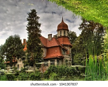 Old house reflection in the pond on a rainy day. Red tiles and cloudy sky. Home looking like castle or palace. Trees and water scenery. Rushes and grass around lakes shore.