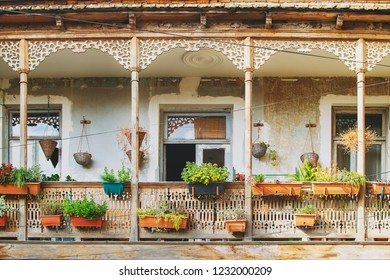 Old House in Tbilisi, Georgia with Beautiful Terrace. Ancient traditional wooden balcony decorated with lot of flowers and old artifacts