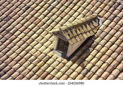 Old house top with traditional roof and a little window