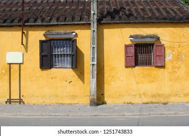 Old house with yellow walls, shutters and wrought iron windows, ancient street in old quarter Hoi An, Vietnam