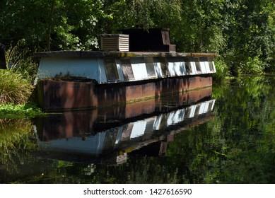 An old houseboat is reflected in the still waters of the beautiful Basingstoke Canal in Surrey