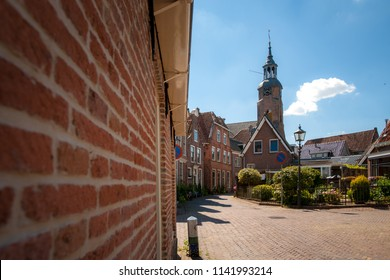 Old houses in a Dutch city with beautifully decorated facades. Streets and see-throughs in an old town in the Netherlands. Historic old town blokzijl