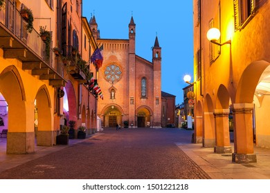Old houses, narrow cobblestone street and cathedral on background in old town of Alba in evening in Piedmont, Northern Italy.