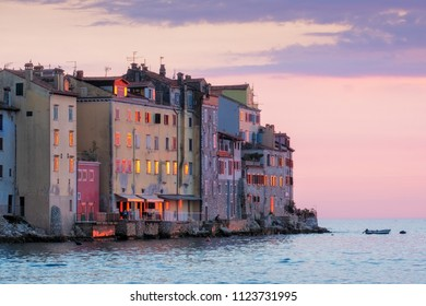 Old houses at ocean coast at colorful sunset in Rovinj, Croatia, Europe