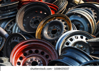 Old hubcaps with no logo. Some rusty, some not. In a heap and abandoned. Red one in front.