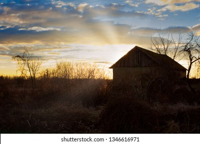 Old Hungarian wooden and pise-built barn house lit by setting sun's lights