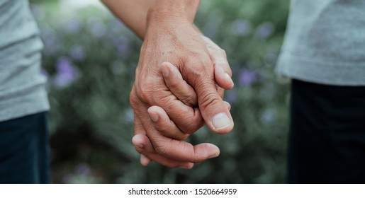 Old husband and wife holding each other hand tightly.