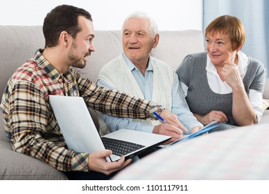 Old husband and wife signing agreement papers with social worker at home
