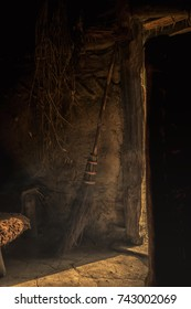 old hut with a floor of mud, a ray of light enters the room through an open door. next to the door there is an old fashioned broom that could be a witches broomstick