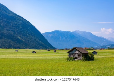 old huts for storing materials and hay on a green meadow in the austrian alps