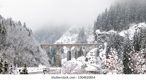 An old iconic Viaduct Bridge spans a snowy winter river anQd roads. The bridge is in a tree lined snow covered valley on a misty and cloud winter day located in Chamonix, France.