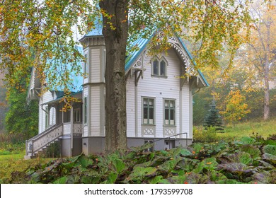 Old idyllic white wooden house with autumn colors in the garden