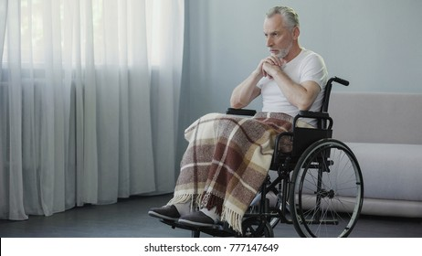 Old ill male sitting in wheelchair and praying, depression and terrible disease