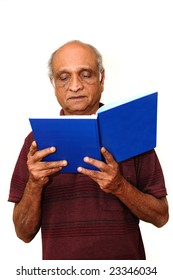 Old Indian Immigrant reading a blue book